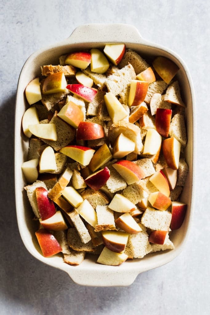 Placing bread and apples in dish for Pecan Apple French Toast Casserole