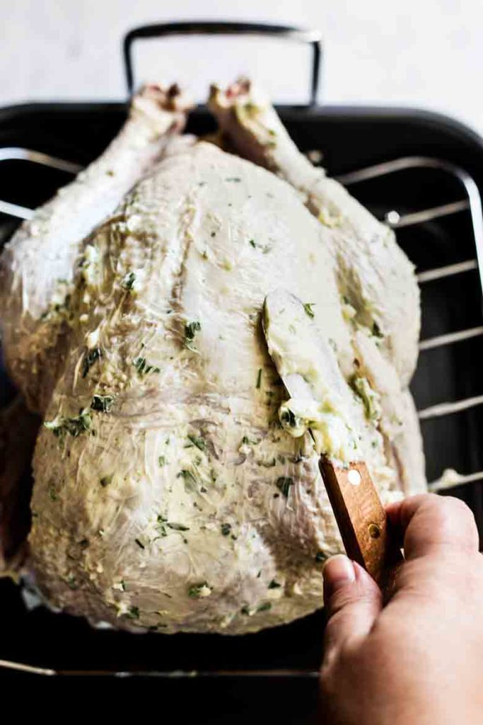 Rubbing garlic butter onto turkey for Roasted Thanksgiving Turkey