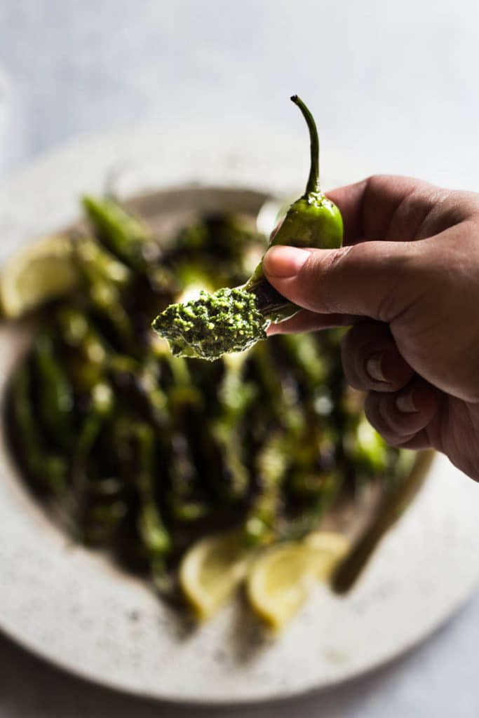 Mildly spicy blistered shishito peppers tossed with olive oil, lemon and salt are paired with a fresh citrus pesto dip for the perfect finger food appetizer.